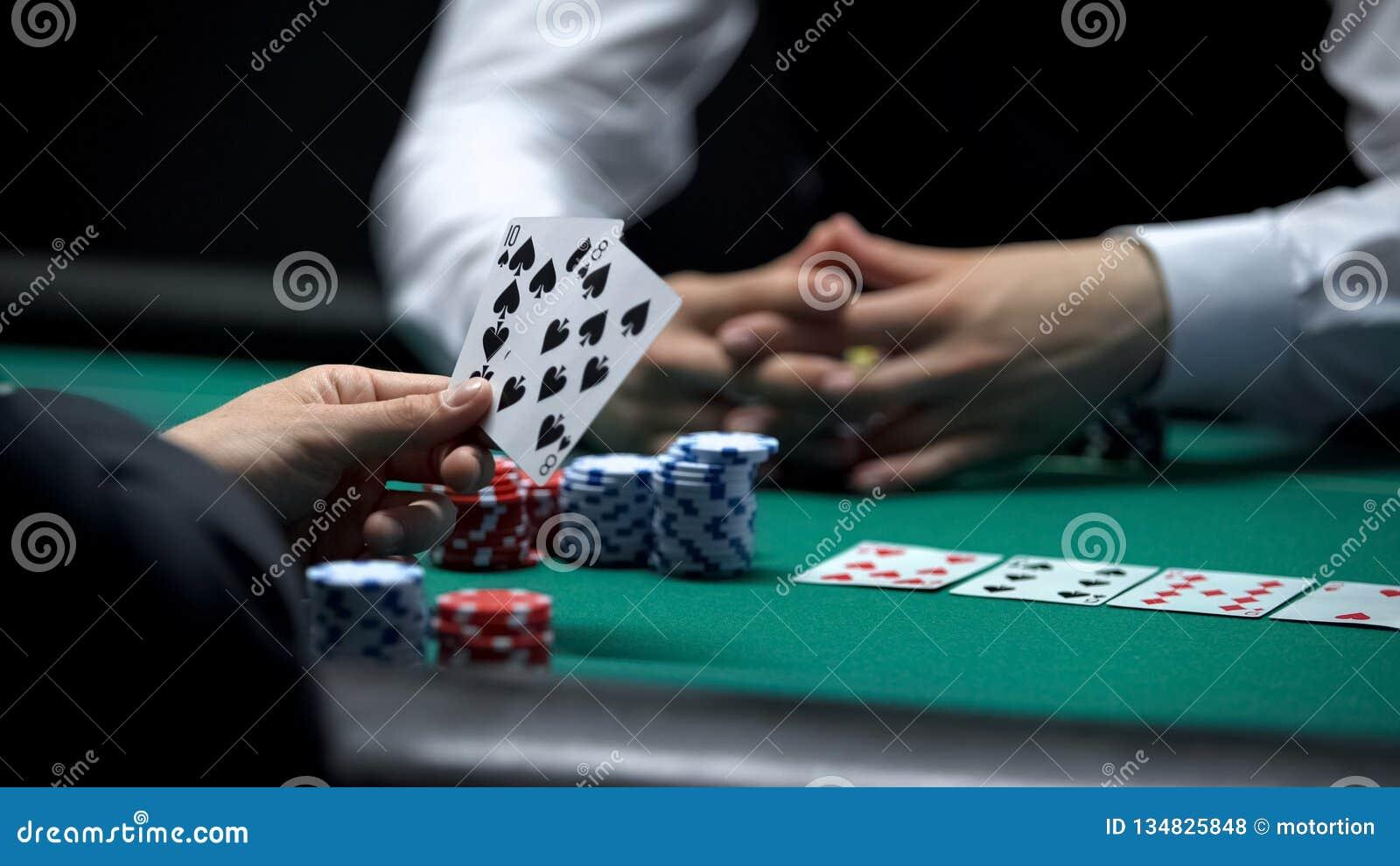 Cliente do casino que tem a combinação fraca da mão no pôquer que faz a aposta grande com as microplaquetas