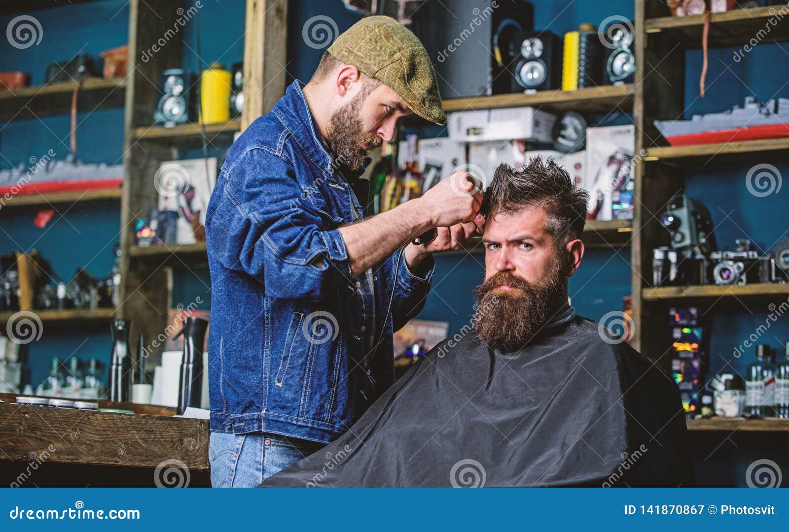Cliente do moderno que obtém o corte de cabelo O barbeiro com tosquiadeira de cabelo trabalha no penteado para o fundo farpado do