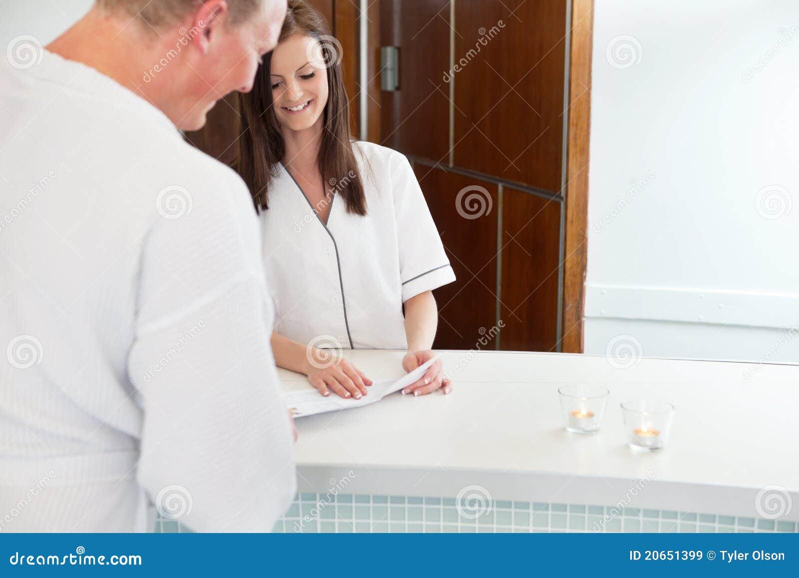 Cliente fêmea do recepcionista e do macho em termas