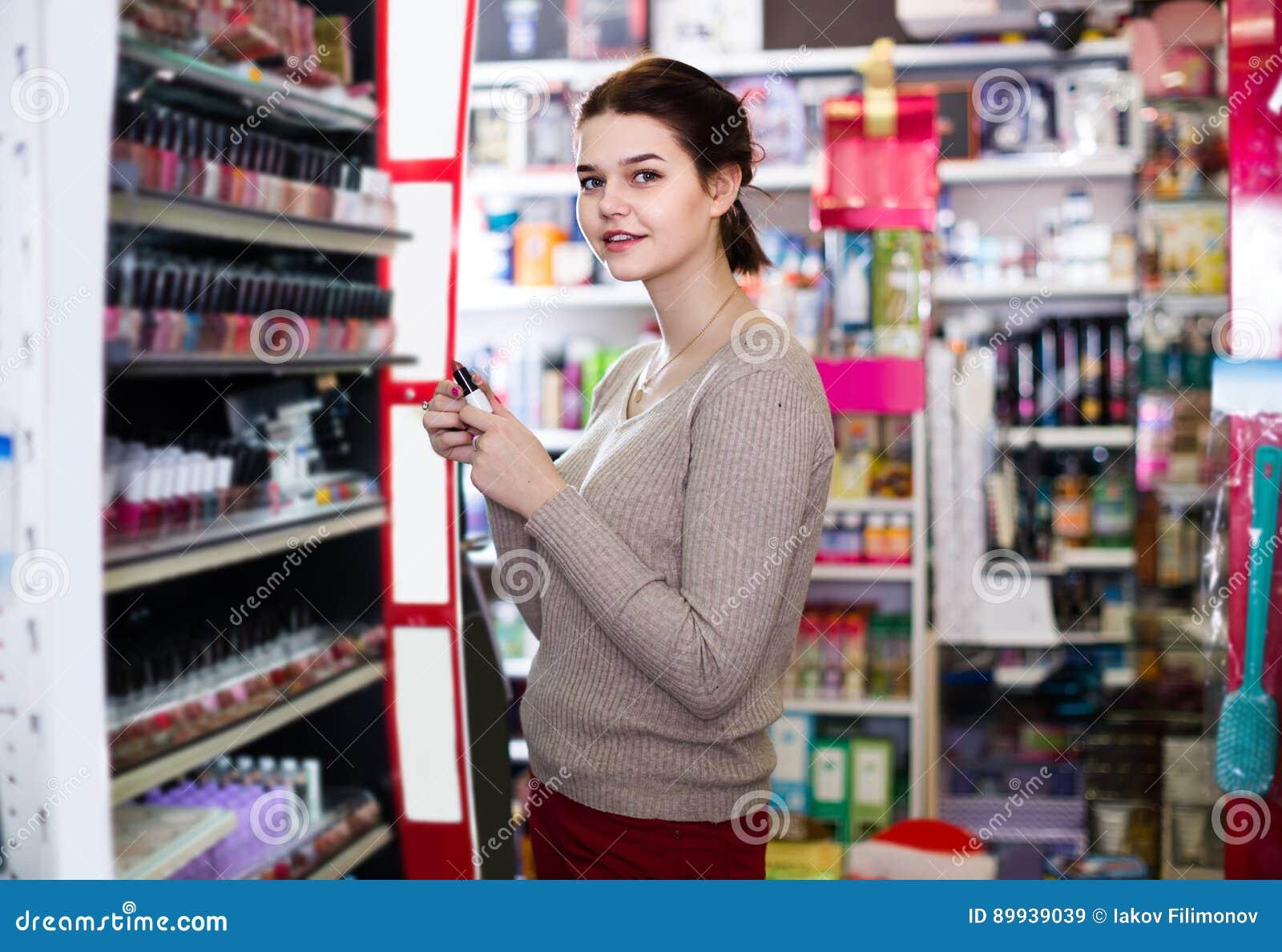 96b1d0ba1 O cliente fêmea feliz de Alemanha que procura o batom nos cosméticos compra