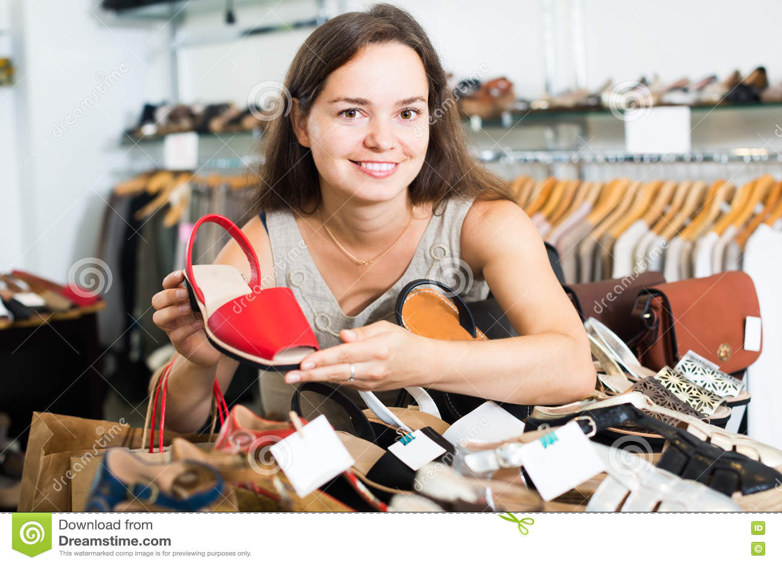 Cliente femenino atractivo que selecciona los zapatos en centro footgear