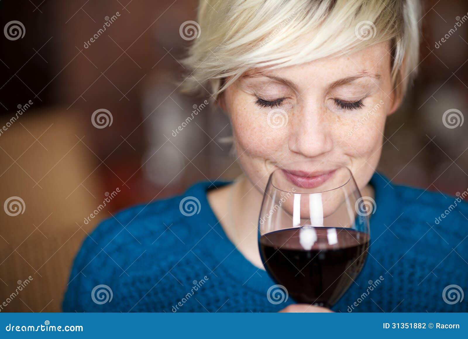 Cliente femenino que bebe el vino rojo con los ojos cerrados