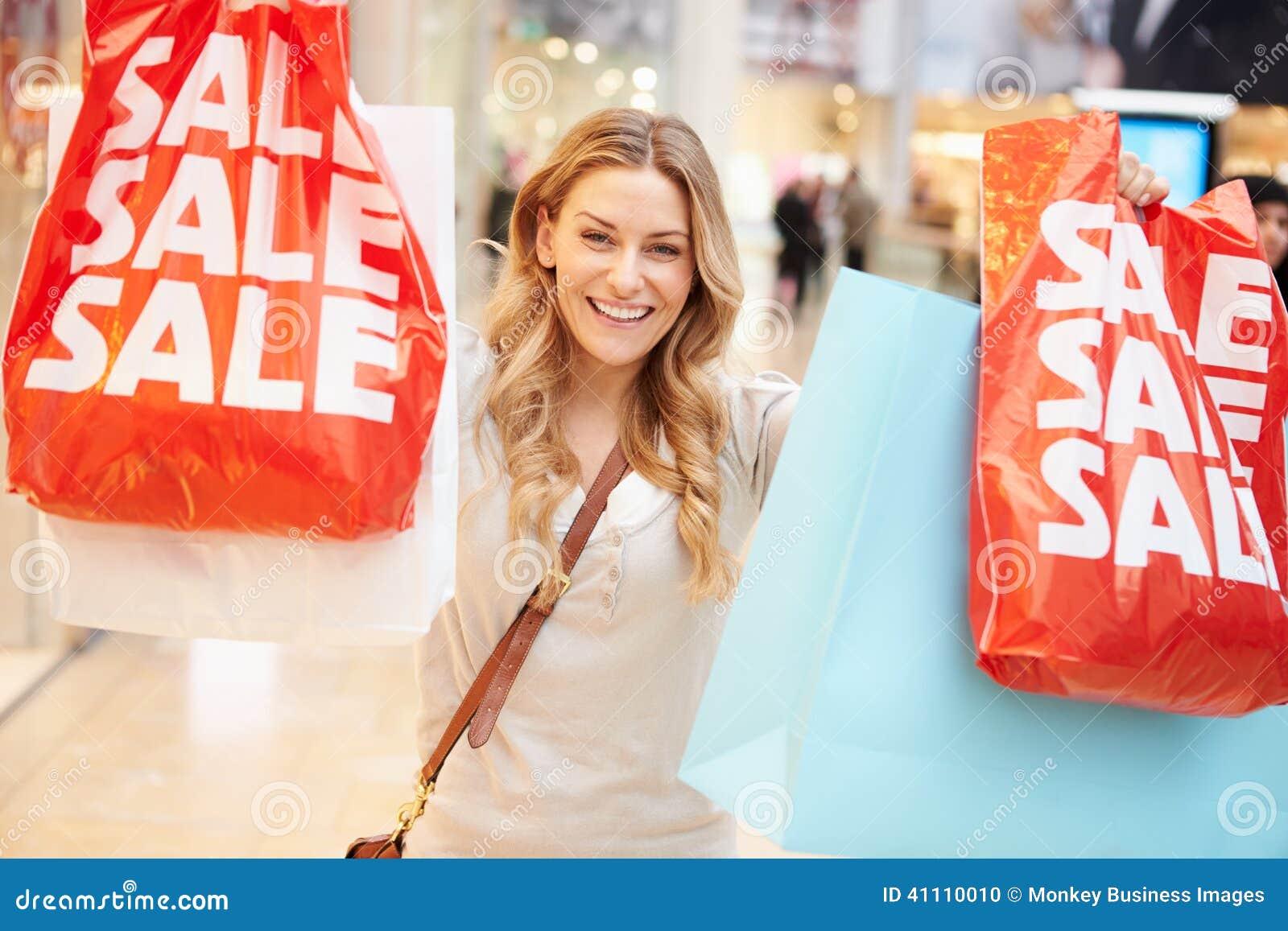 Cliente femminile emozionante con le borse di vendita in centro commerciale