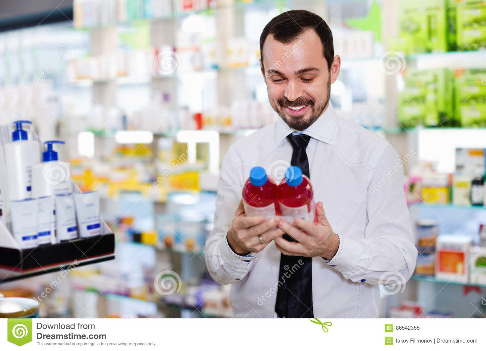 ed41a04cd Cliente feliz de sorriso do cmale que procura a medicina direita na farmácia