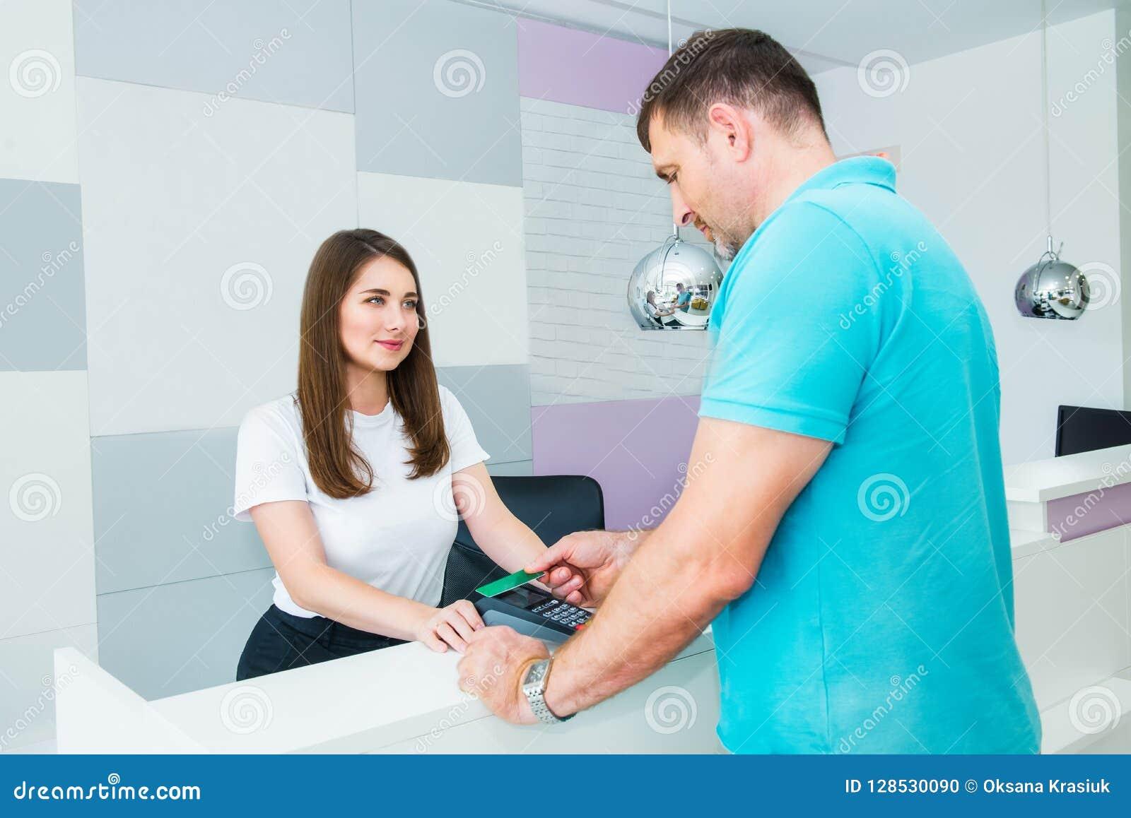 Cliente que faz o pagamento sem contato com o cartão de crédito da tecnologia do nfc na loja, clínica, hotel Gerente administrati