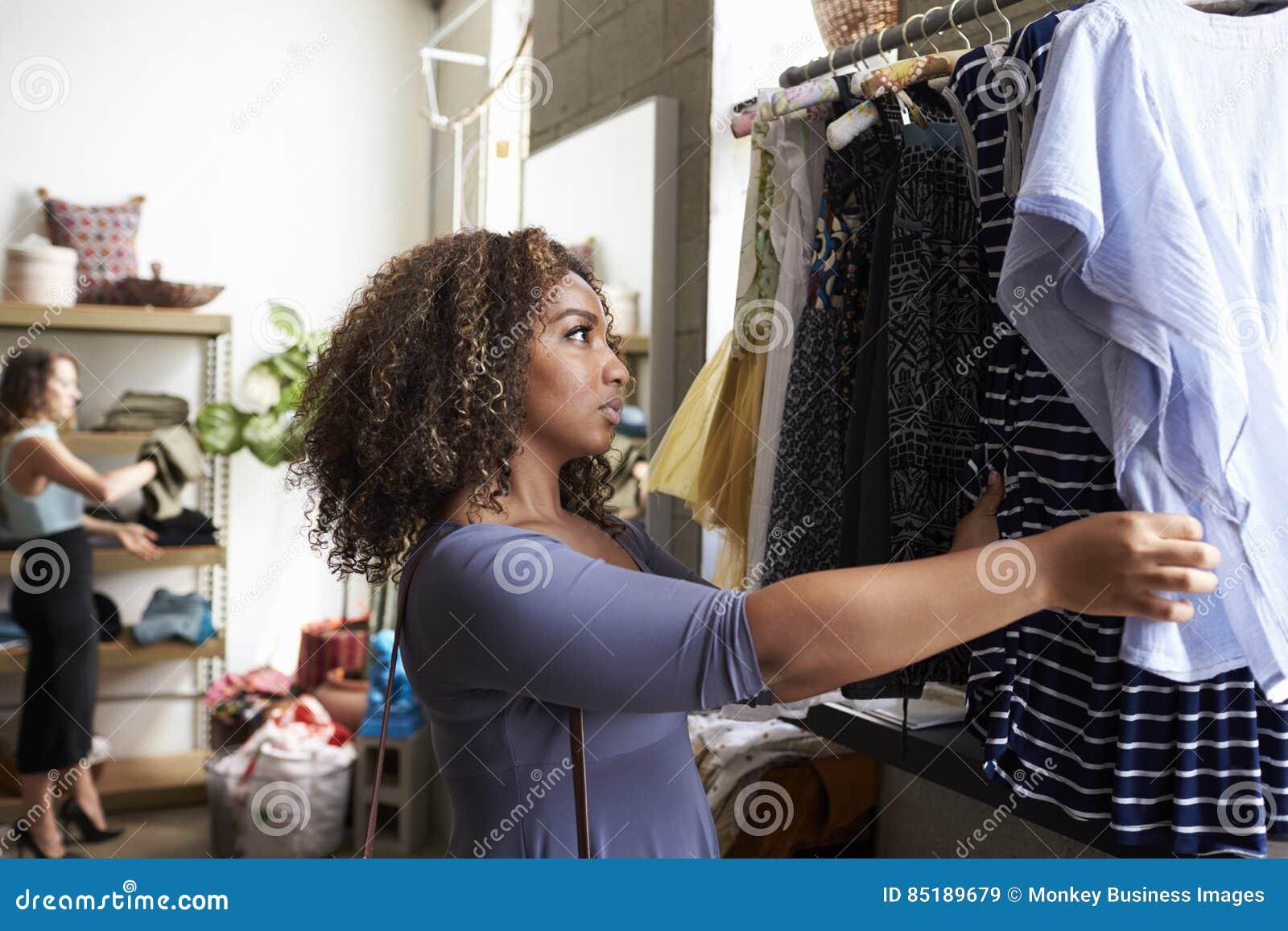 Cliente que olha a roupa em um trilho de suspensão em um boutique
