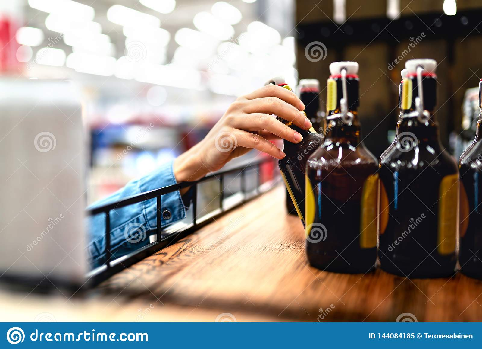 Cliente que toma la botella de cerveza del estante en licorería Relleno y media del alcohol de la mujer que hacen compras o del p