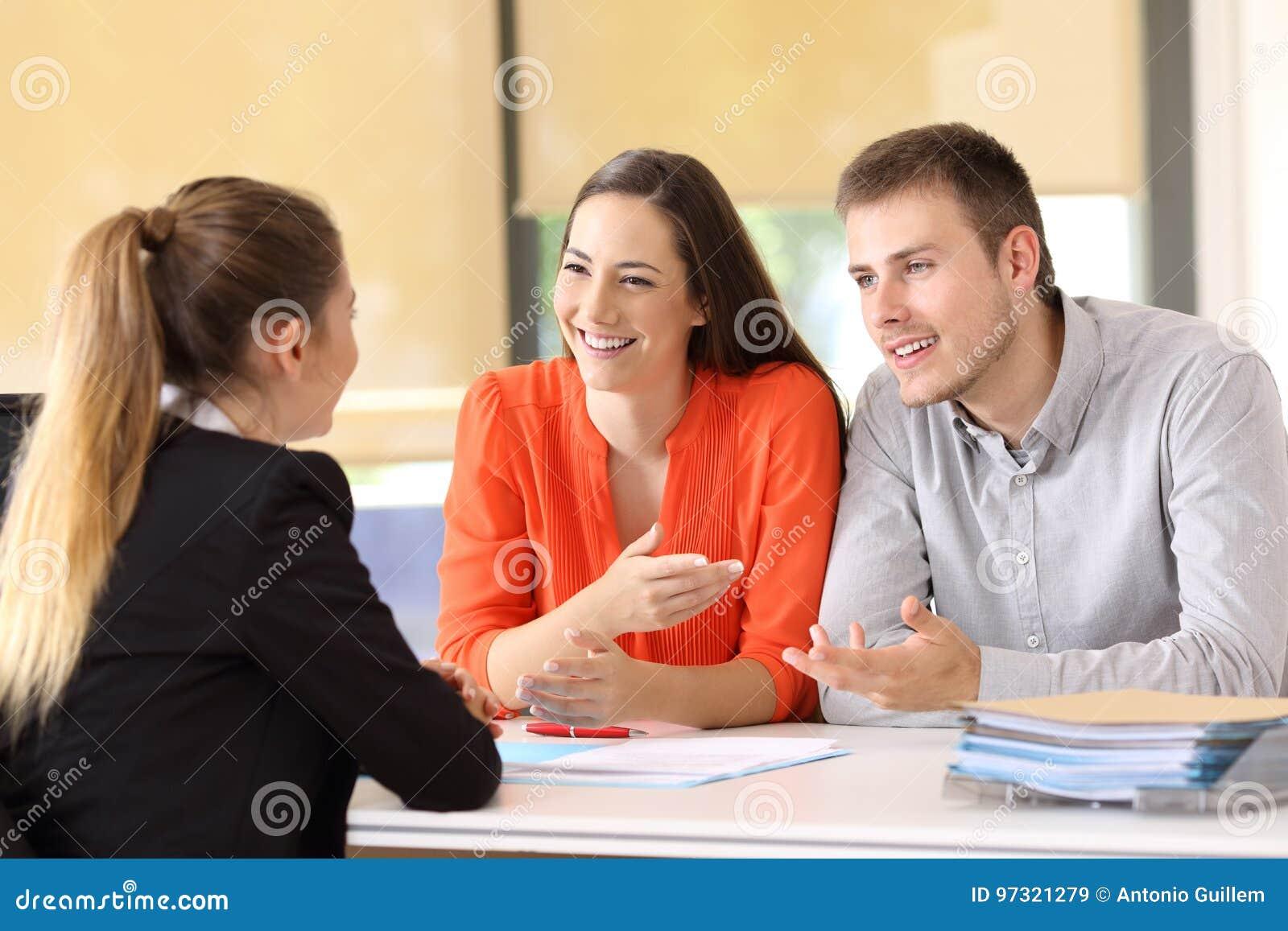 Clientes felices que hablan con el oficinista