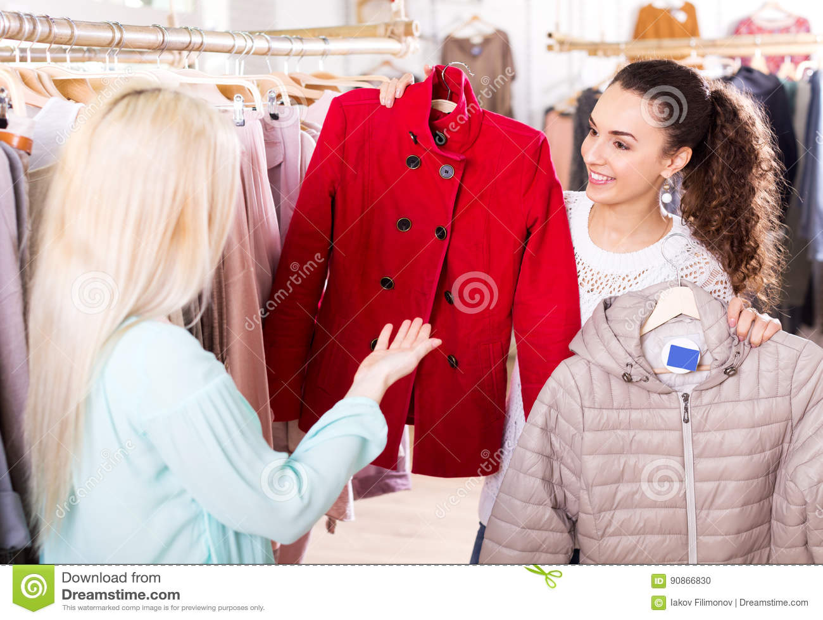 Clientes femeninos que seleccionan las capas y las chaquetas