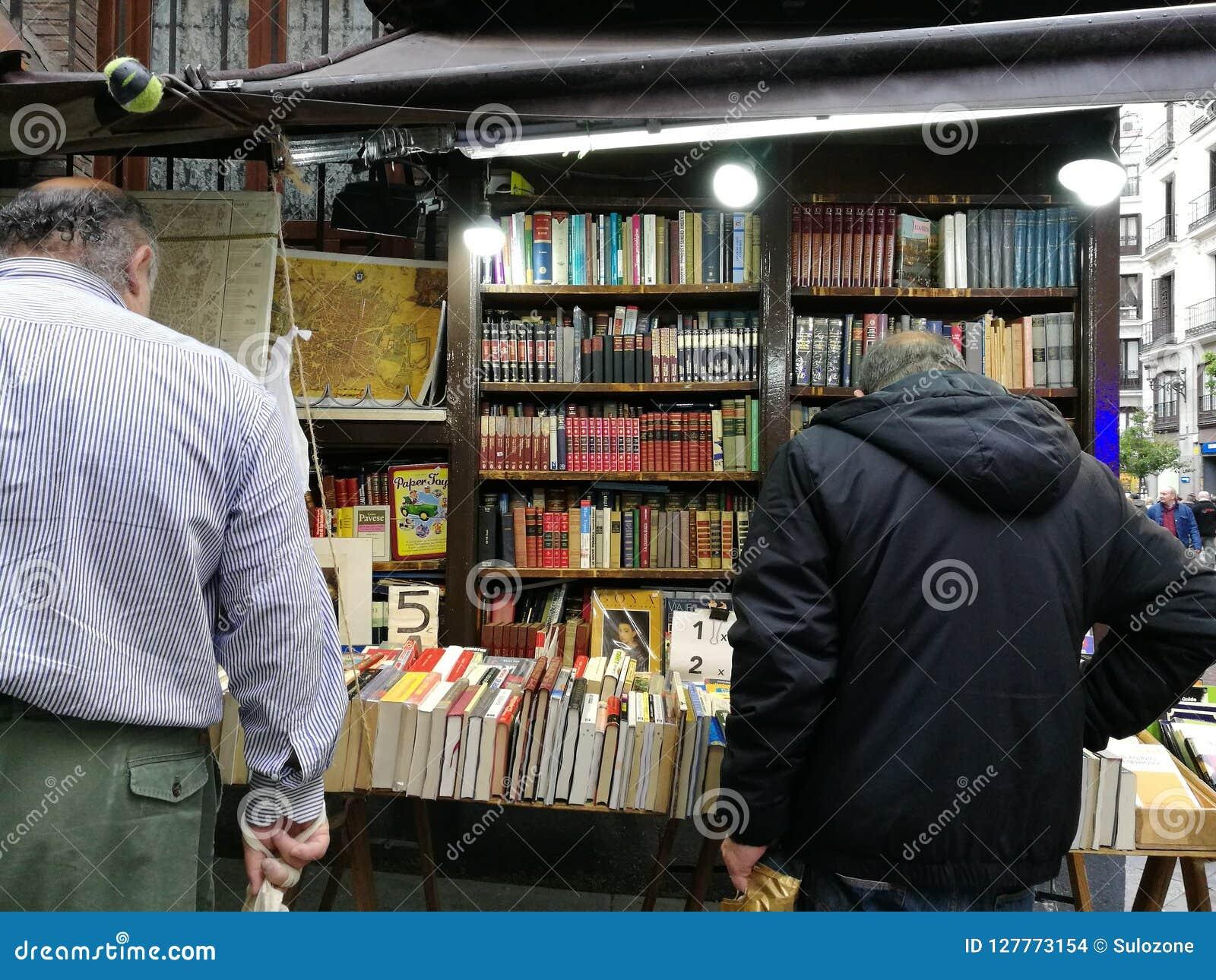 Clientes que eligen los libros usados en una librería de la calle
