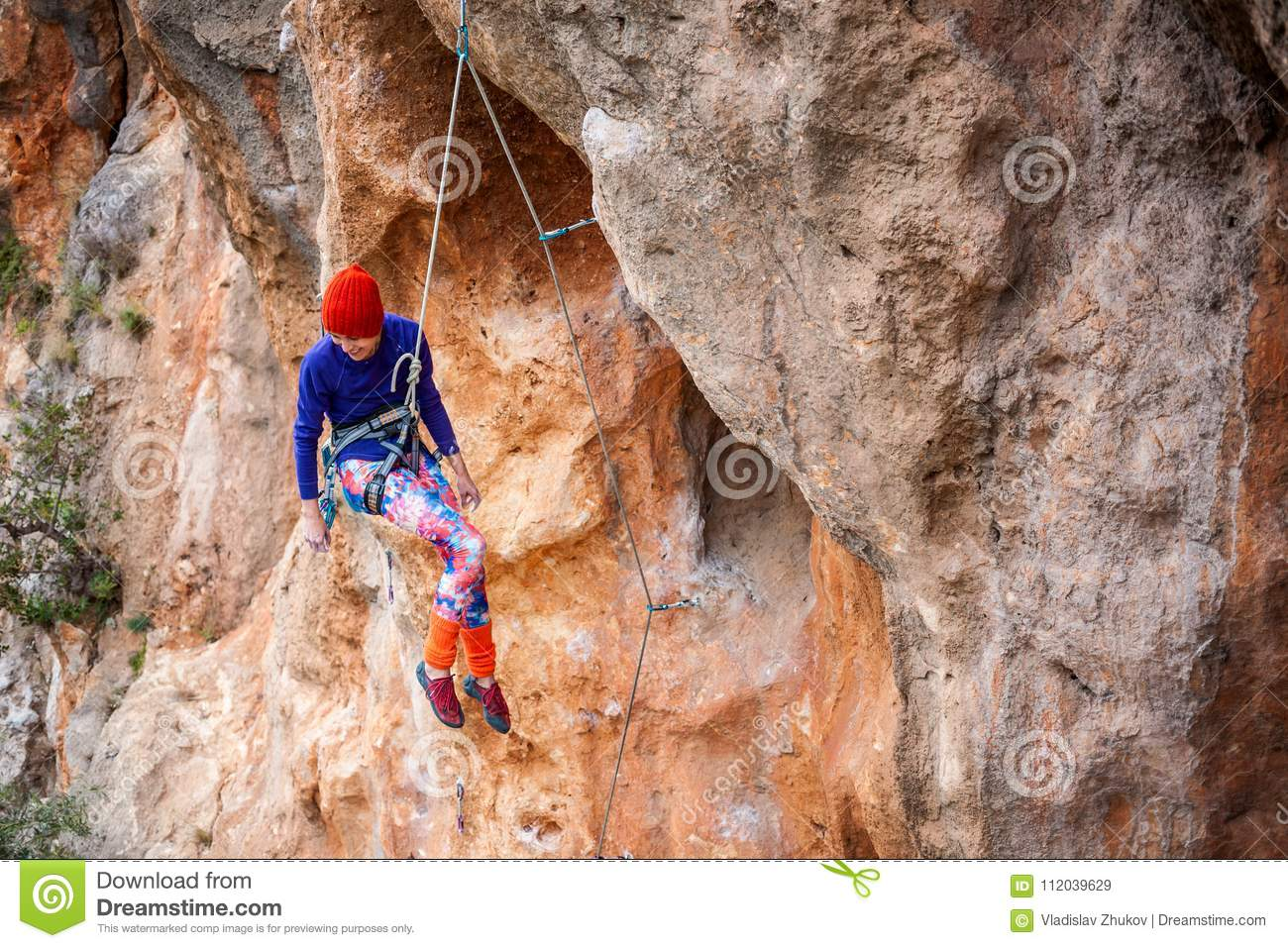 The climber is hanging on a rope.