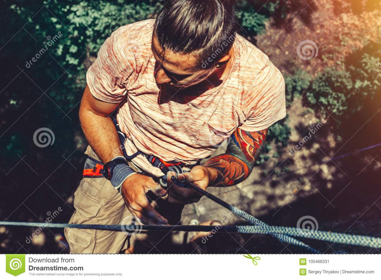 Climber Man Hanging On A Rock On A Rope And Looks Somewhere On The Wall. Extreme Lifestyle Outdoor Activity Concept
