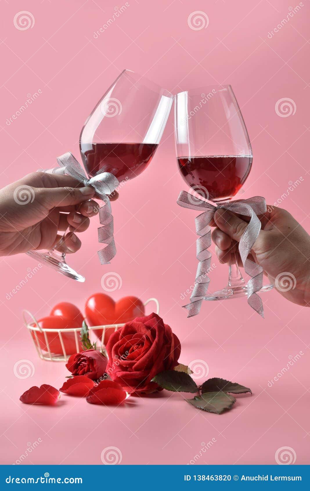Clinking стекла красного вина в руках, с красной розой на дне на розовой предпосылке Концепция дня ` s валентинки