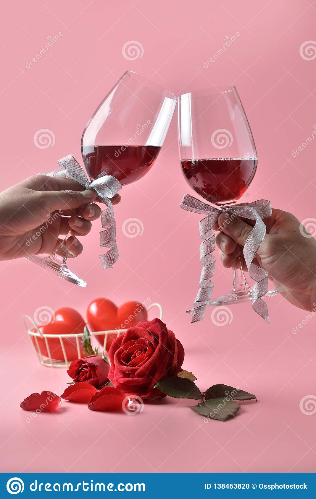Clinking glasses of red wine in hands, with red rose on the bottom on pink background. Concept of Valentine`s Day