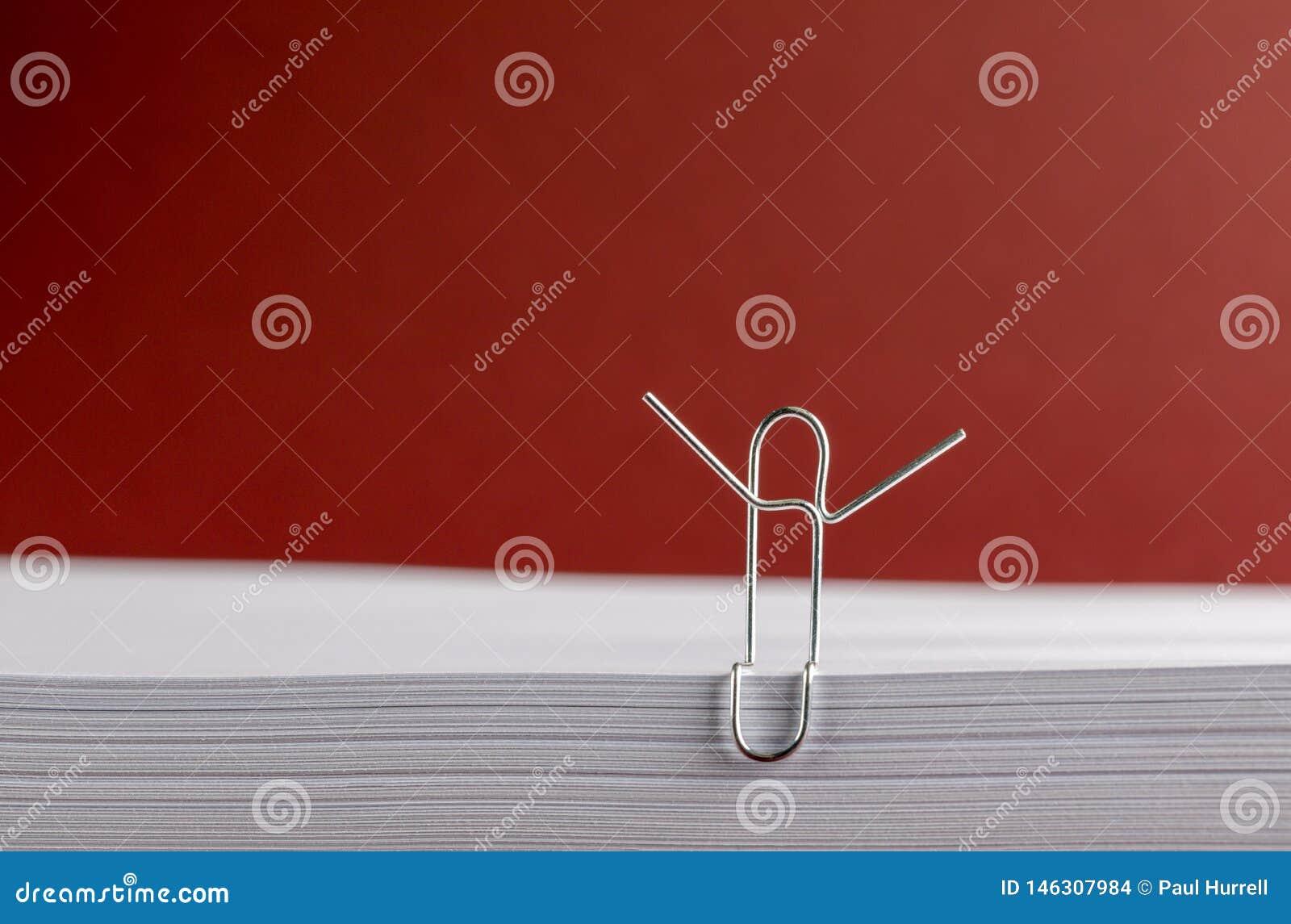 Clipe de papel com mãos no alto no Livro Branco no fundo vermelho