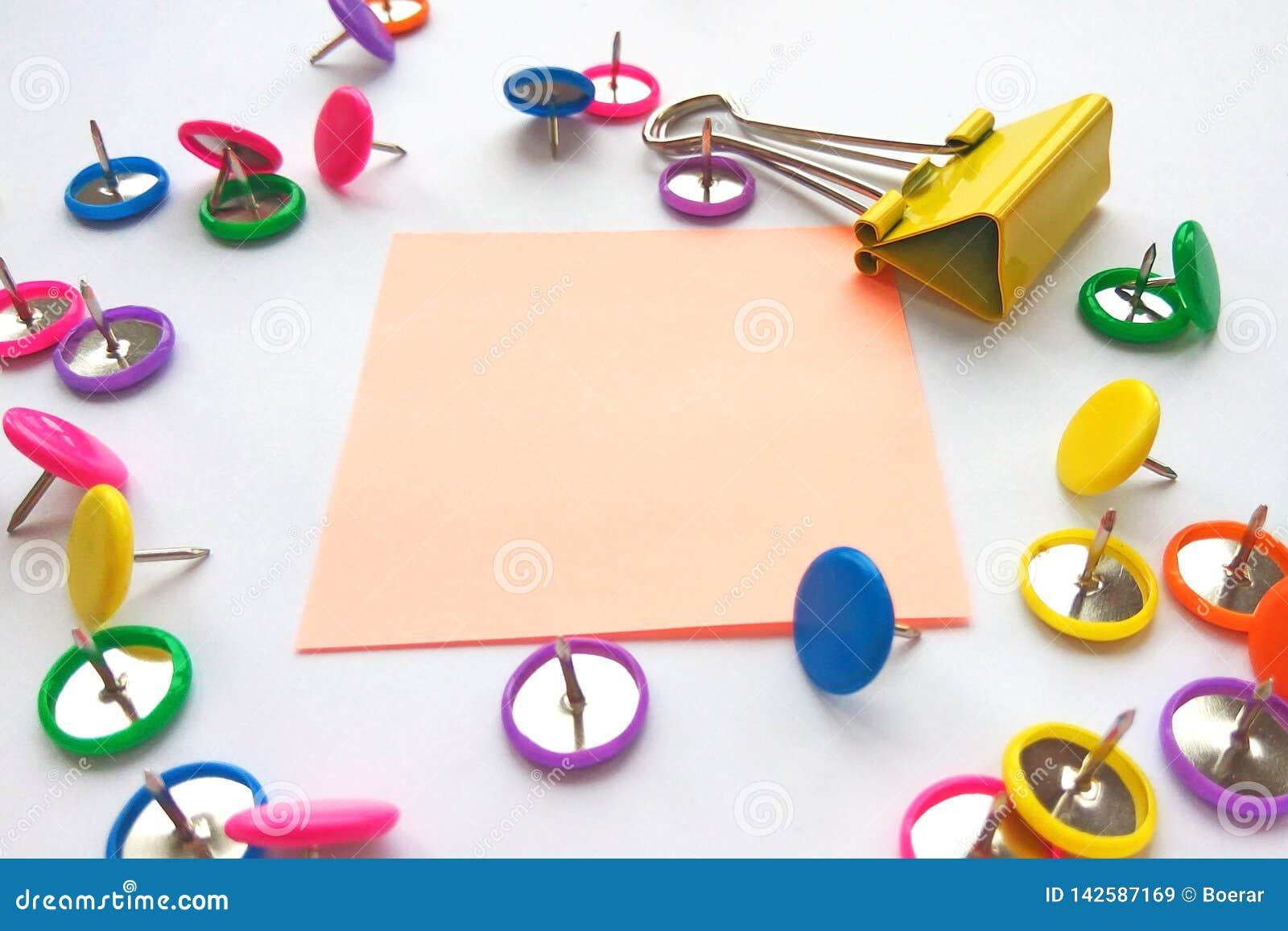 Clipes de papel da escola e dos materiais de escrit?rio, pinos, notas, etiquetas no fundo branco Zombaria acima