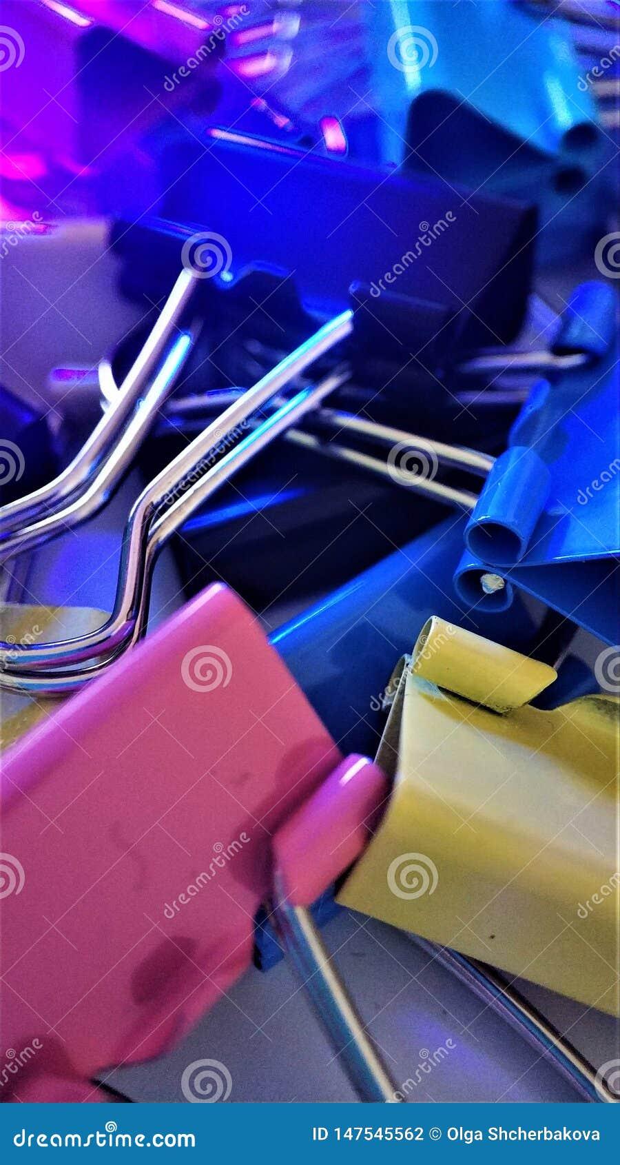 Clips de papel coloreados bajo rayos del primer macro ultravioleta para el fondo