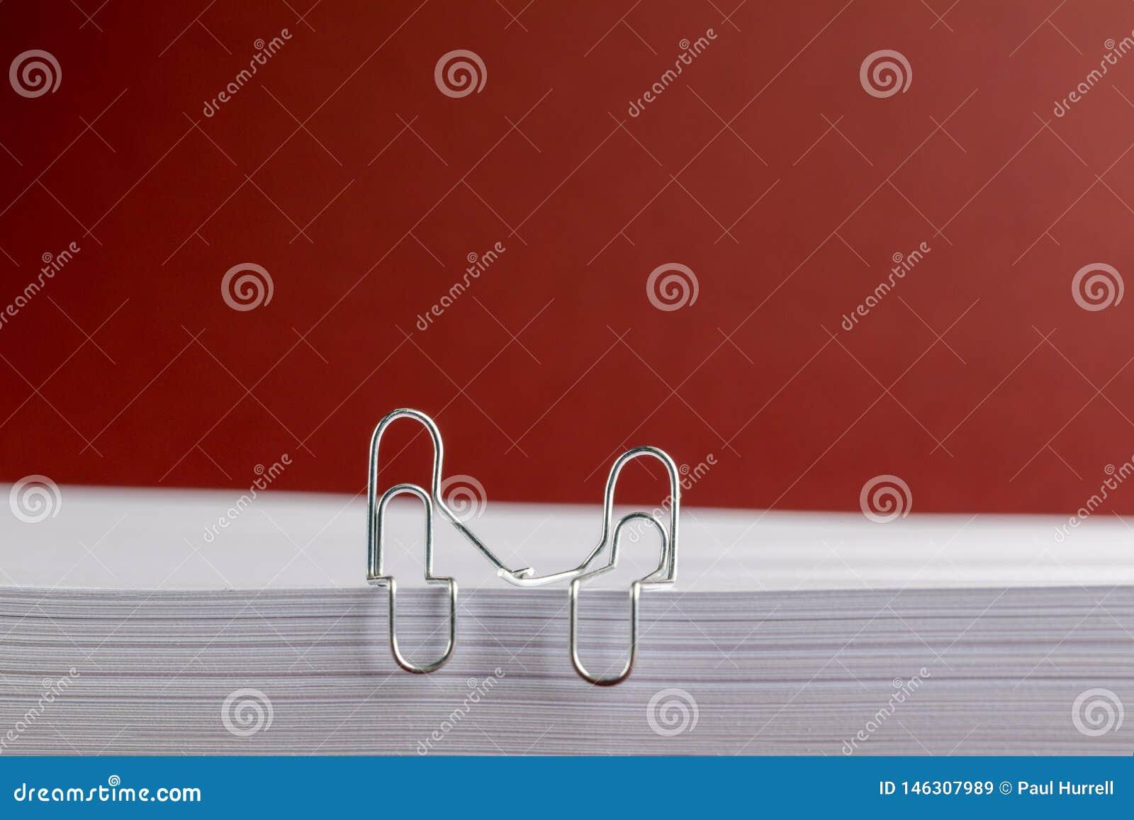 Clips de papel que llevan a cabo las manos en la pila de papel en fondo rojo