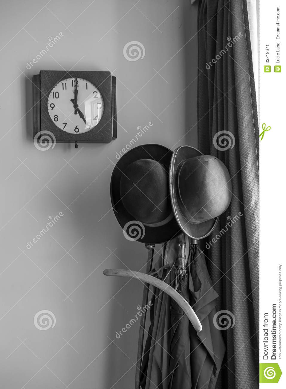 A clock showing 5 o clock next to bowler hats on a stand