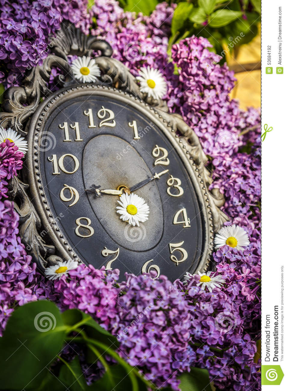 Clock surrounded by spring flowers. Shallow depth of field with selective focus on clock. Lilac flowers