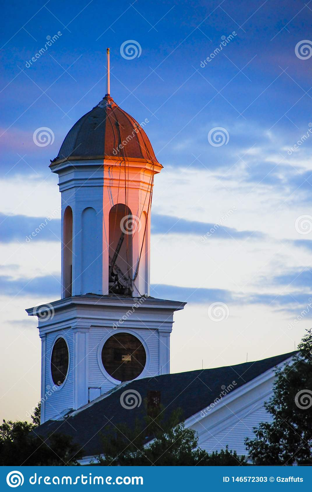Clock tower at sunset with blue sky and clouds