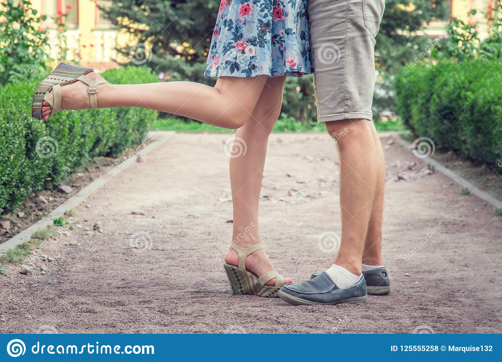 Close the legs of young men and women during a romantic date in a green garden.