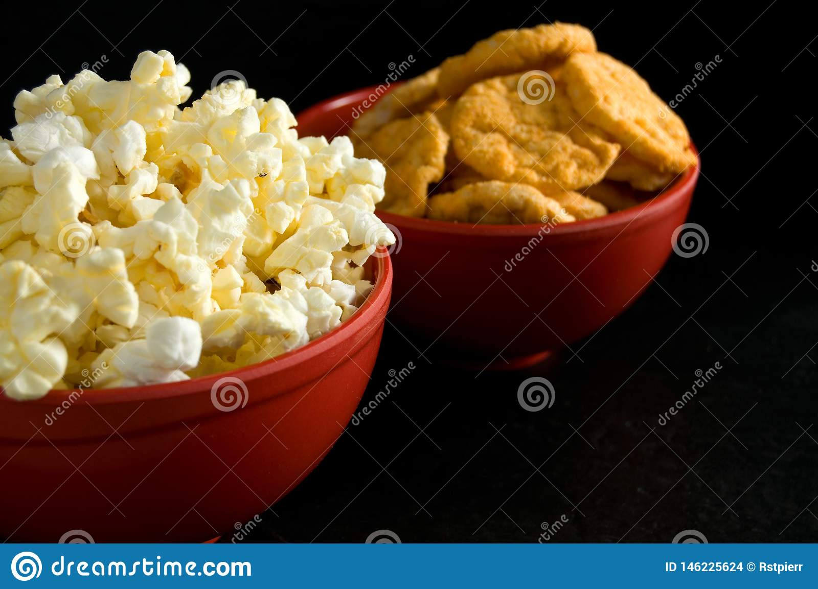 Close Side View Of Buttered Popcorn And Bbq Rice Chips In Red Bowls Isolated On Black Stock Photo Image Of Pleasure Corn 146225624