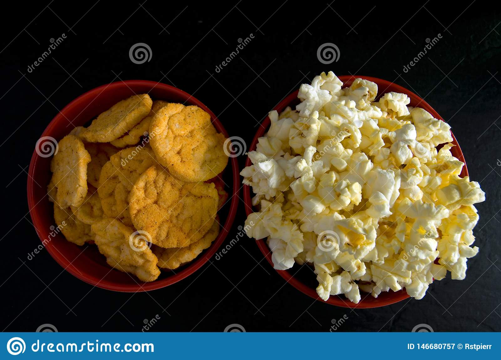 Close Top View Of Buttered Popcorn And Bbq Rice Chips In Red Bowls Isolated On Black Stock Image Image Of Drink Delicious 146680757