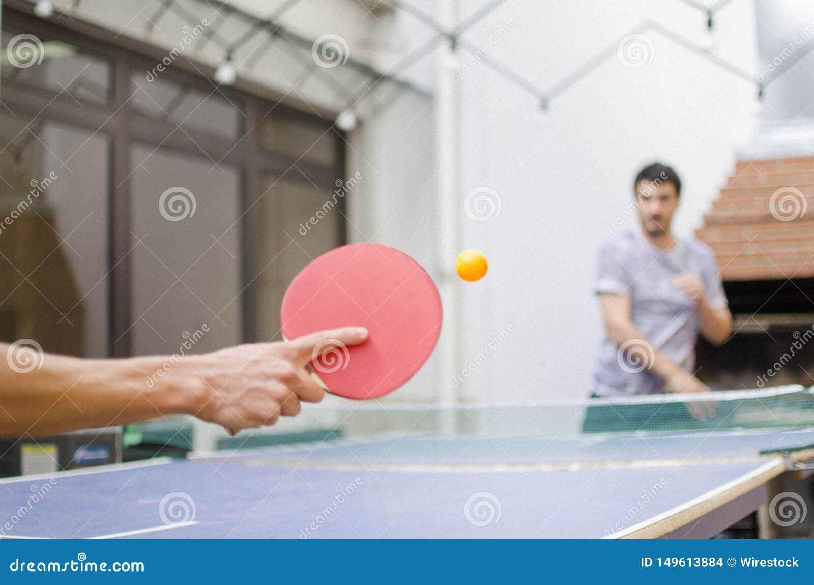 Close up à mão de um desportista que joga o tênis de mesa