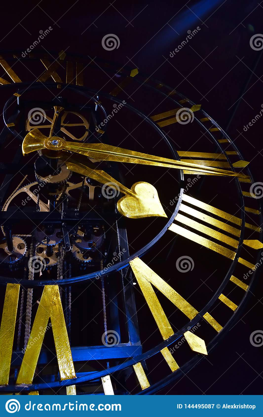 Close-up of ancient dark skeleton clock with golden hands and roman numerals