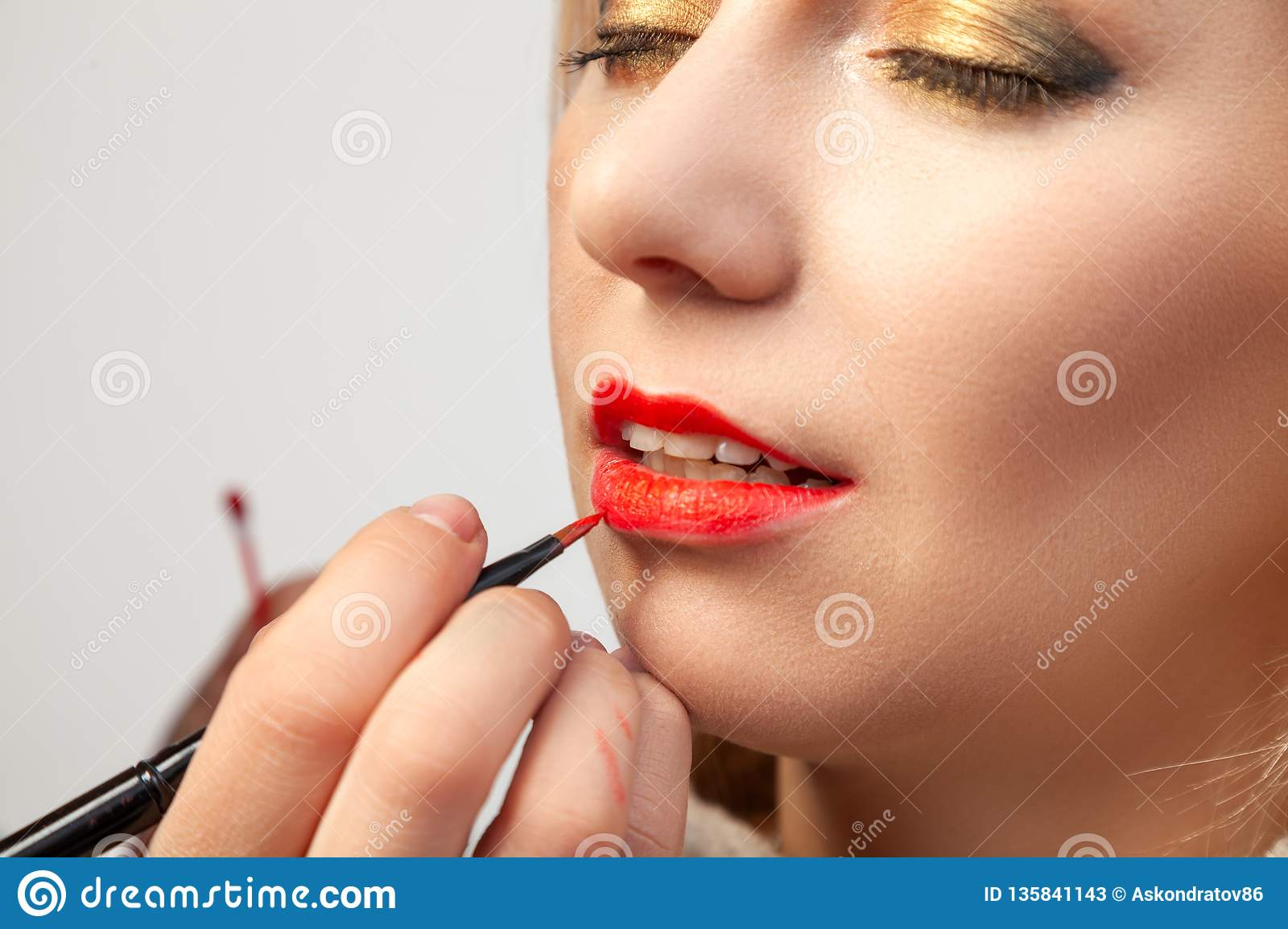 Close-up applying on the lips, the make-up artist holds a brush in her hand and applies red lipstick on the model`s open mouth