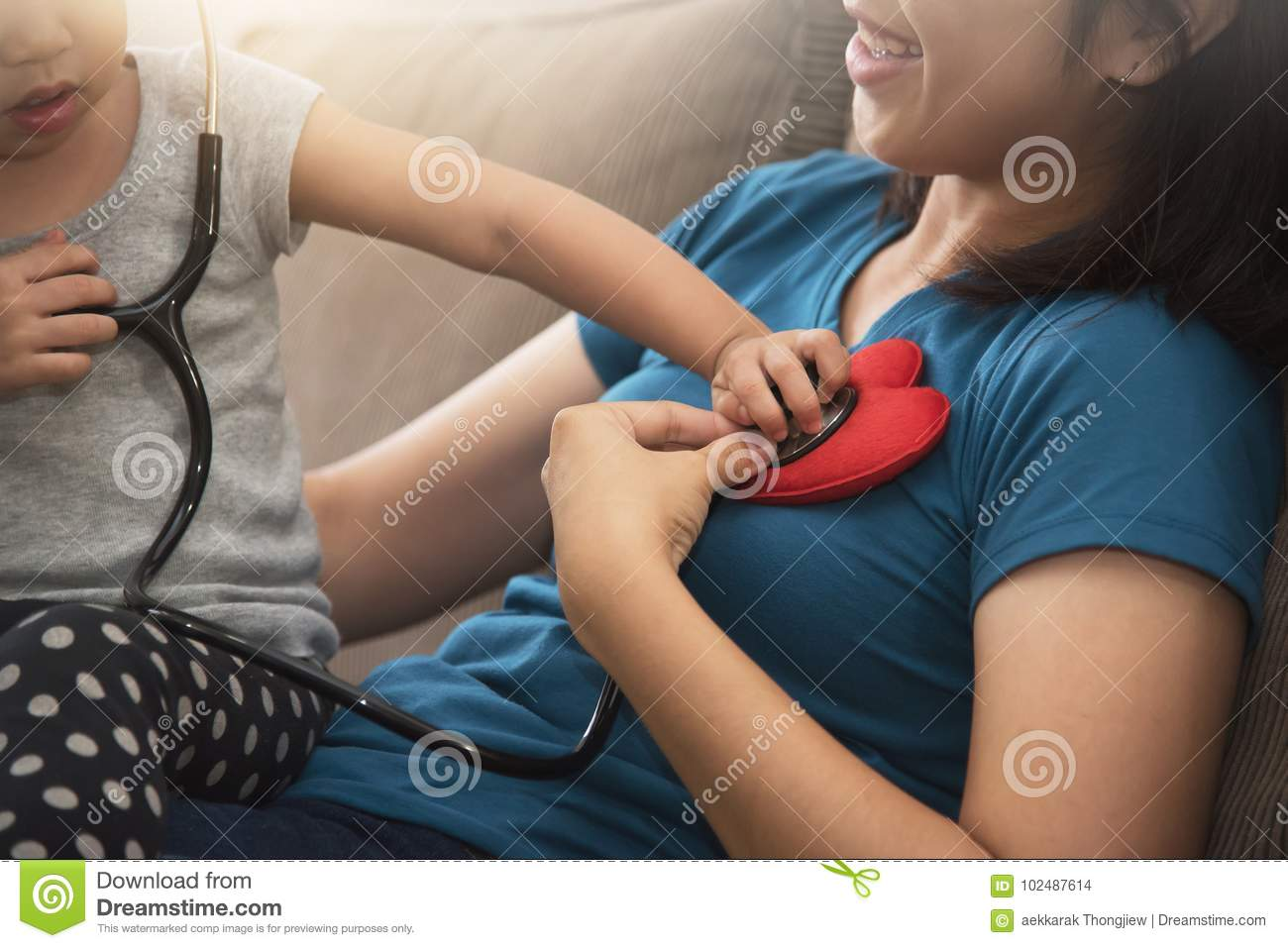 Close up of Asian little kid girl examining heartbeat.