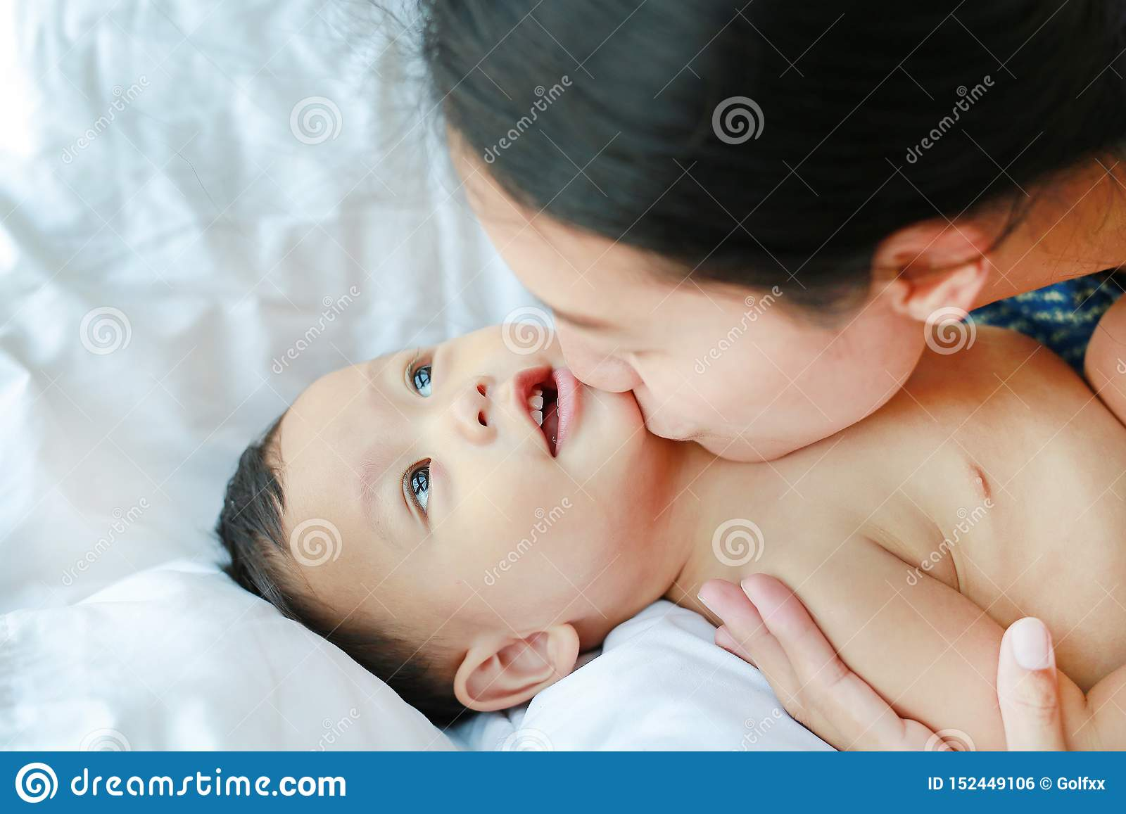 Close-up Asian mom playing and kissing her little baby boy on the bed