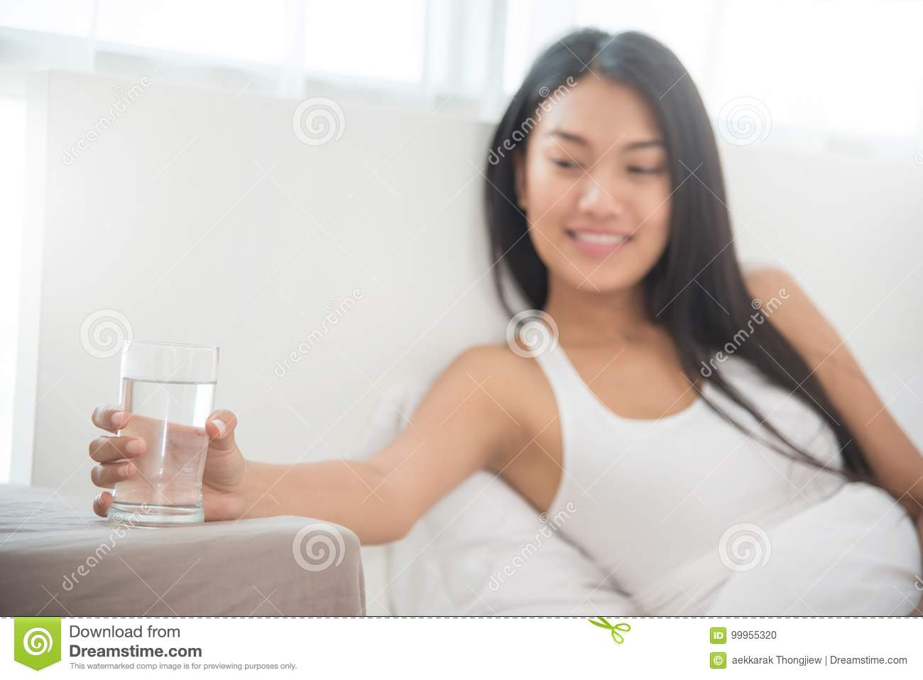 Close up Asian Woman holding glass of water.