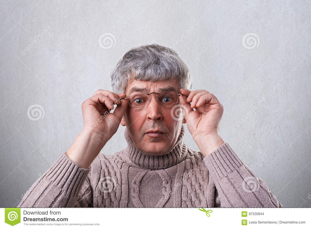 A close-up of astonished senior man wearing glasses and sweater holding his hands on the frames of glasses looking with wide opene
