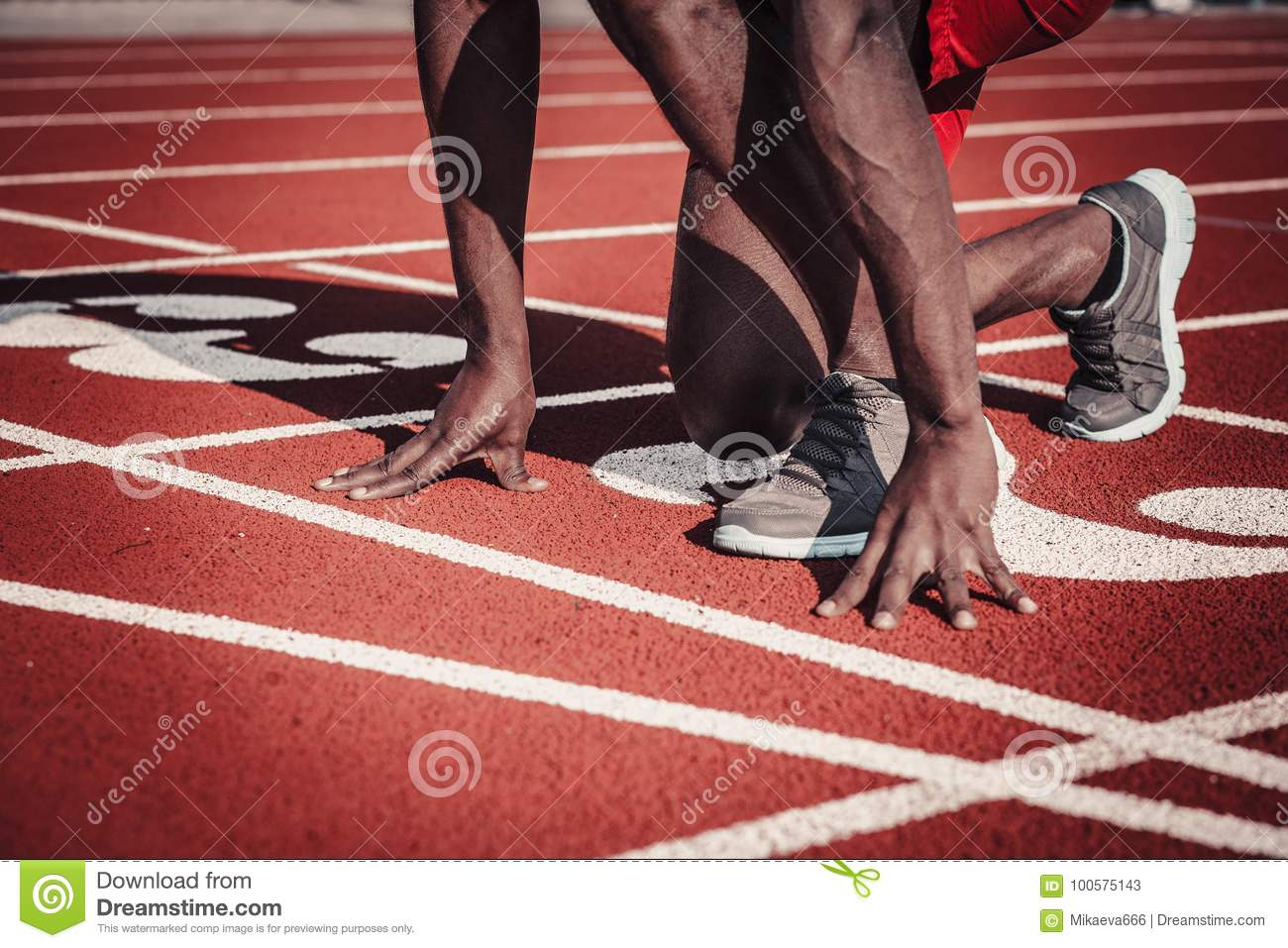 Close-up of the athlete`s hand and foot plan push off the track at the stadium