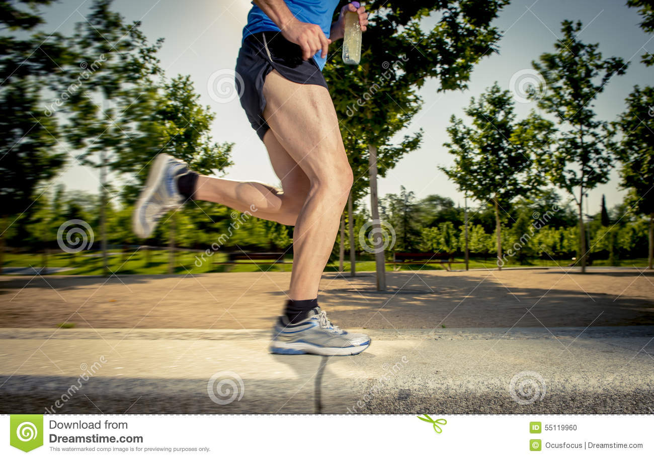 Close up athletic legs of young man running in city park with trees on summer training session practicing sport healthy lifestyle