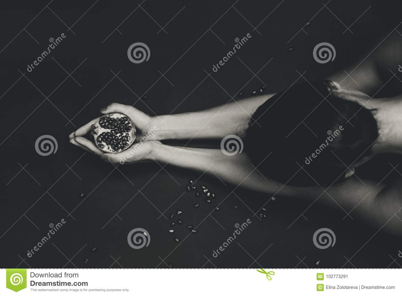 Close up of attractive young woman with pomegranate at black