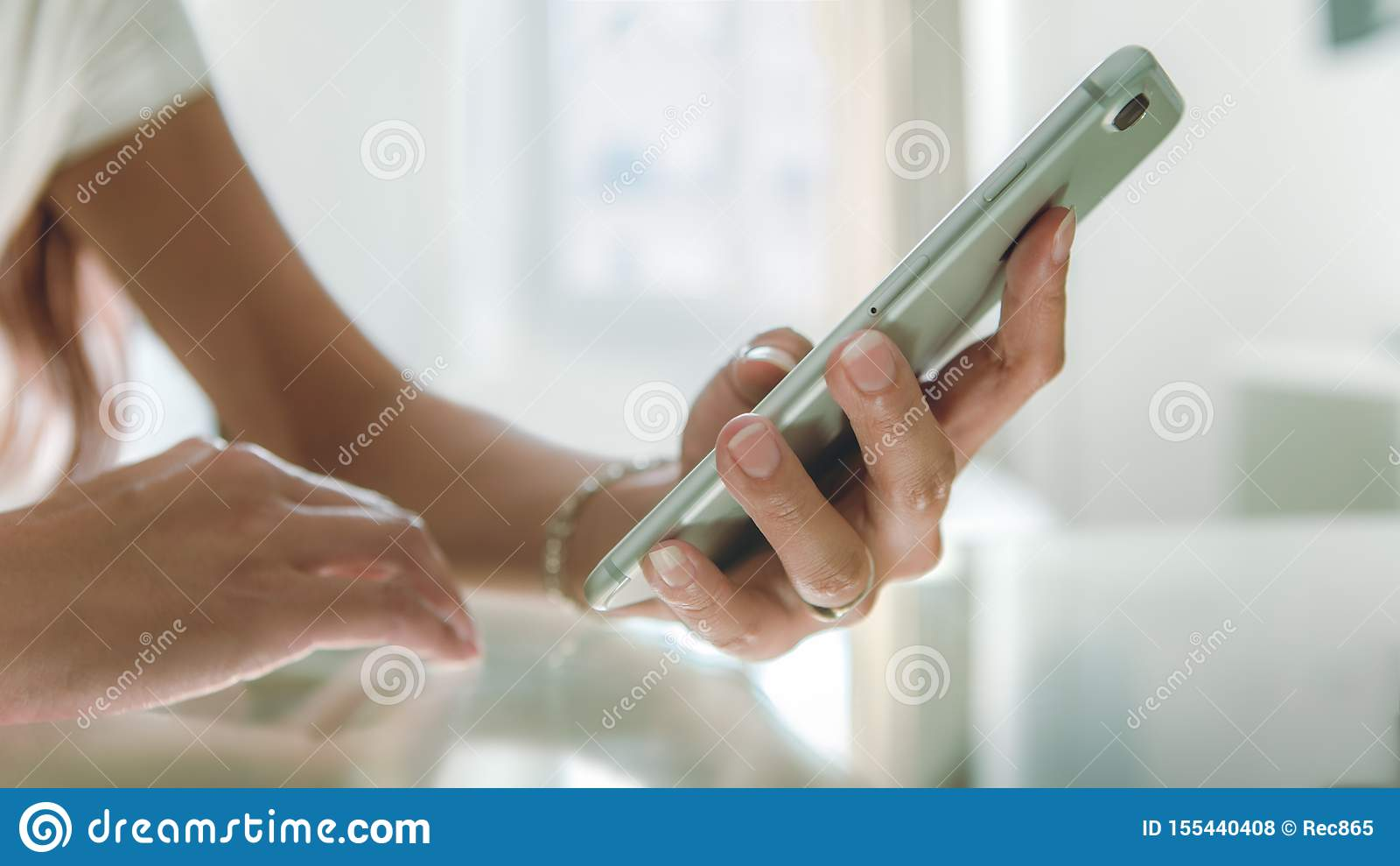 Close-up Aziatische hand die smartphone op glaslijst gebruiken bij mooi wit huis