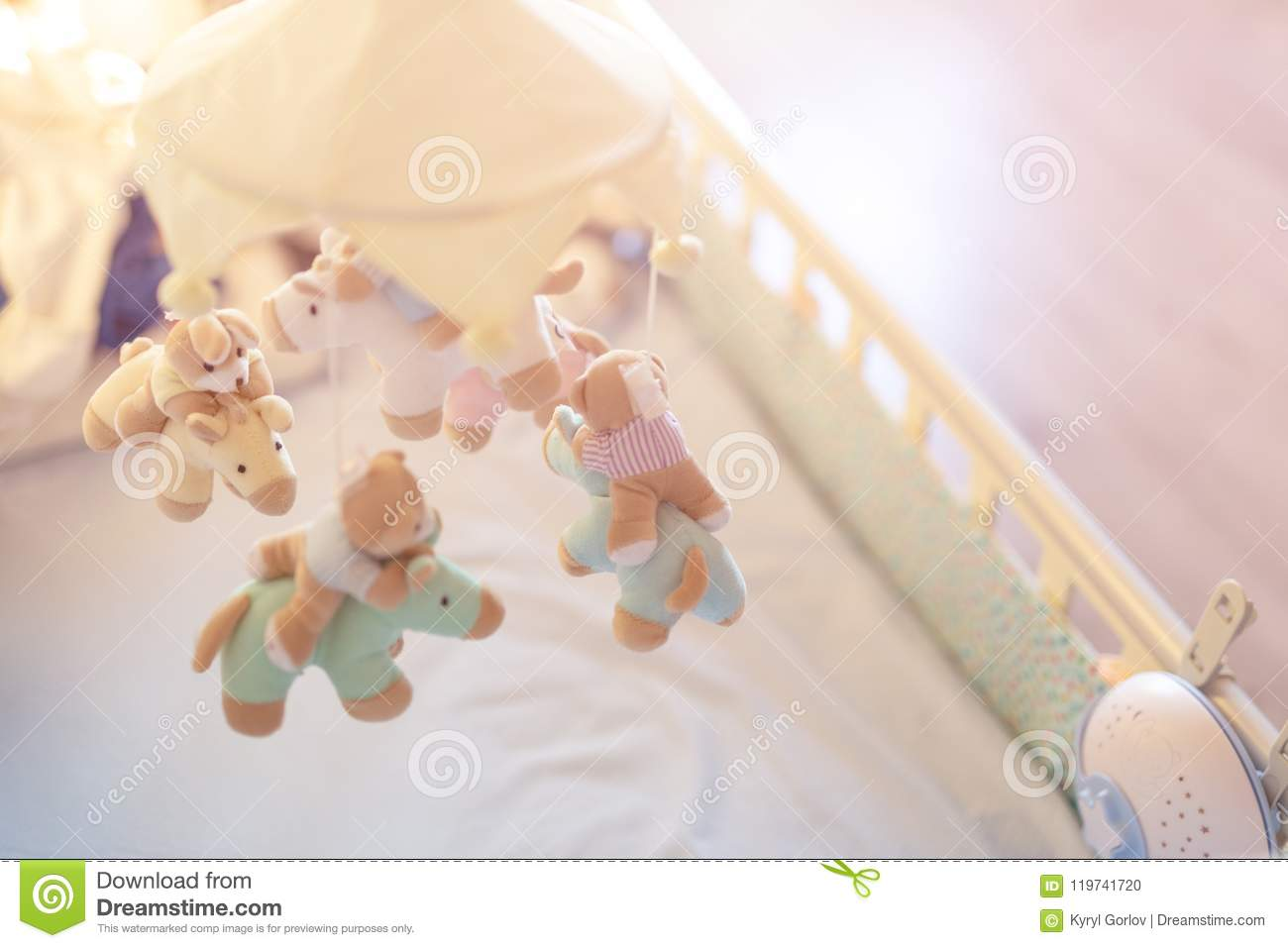 Close-up baby crib with musical animal mobile at nursery room. Hanged developing toy with plush fluffy animals. Happy parenting an