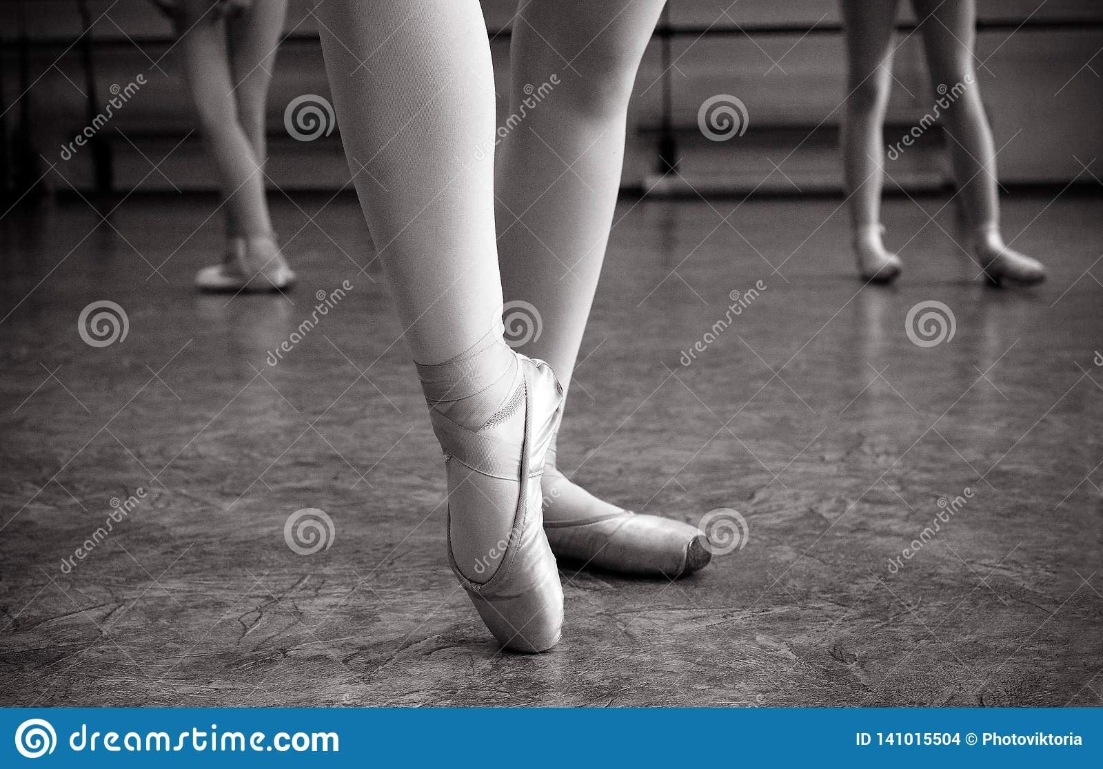 Close-up of ballerina feet on pointe shoes in the dance hall. Vintage photography. Close-up of a ballerina in the dance hall.