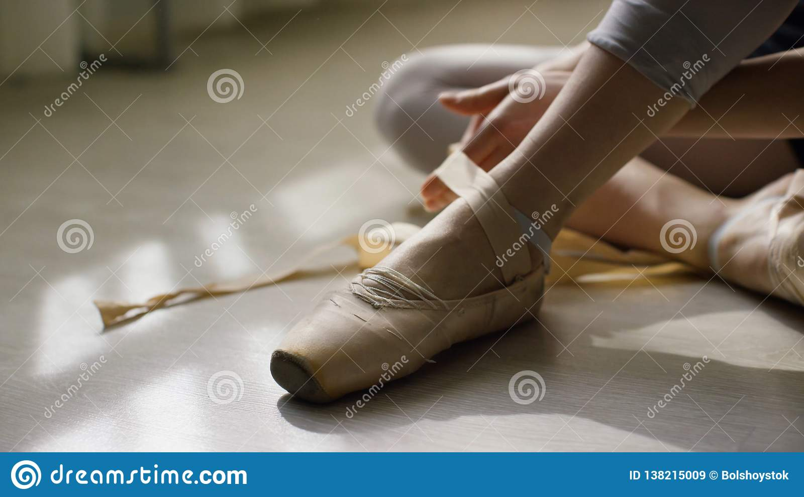 Close-up of ballerina`s feet. Ballerina preparing for training, and tying ribbon of pointe shoes sitting on floor in