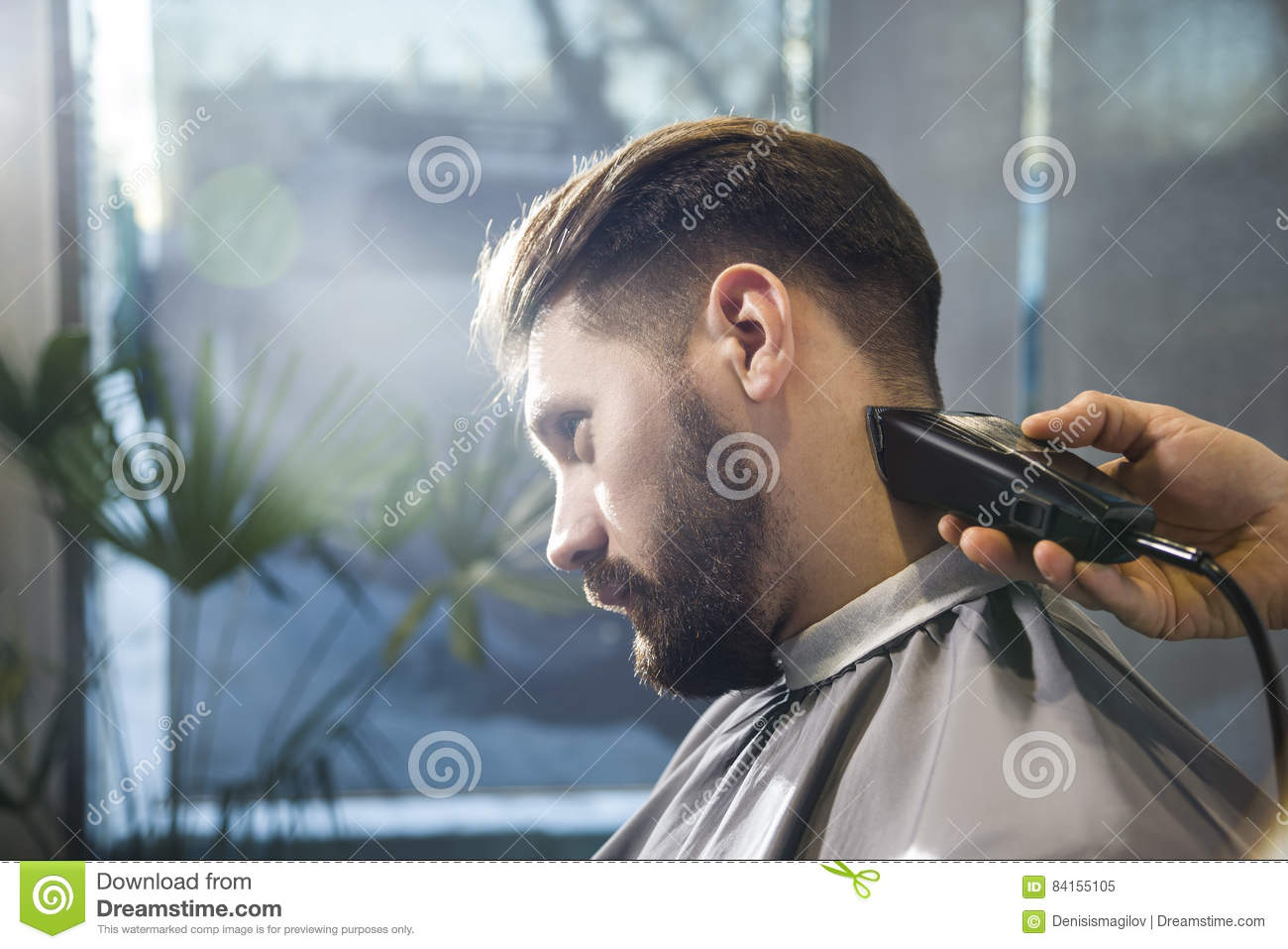 Close up of barber's hands trimming a serious businessman's hair.