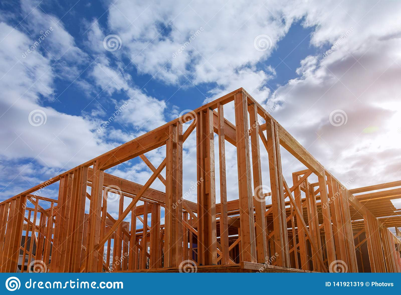 Close-up of beam built home under construction and blue sky with wooden truss, post and beam framework. Timber frame house, real