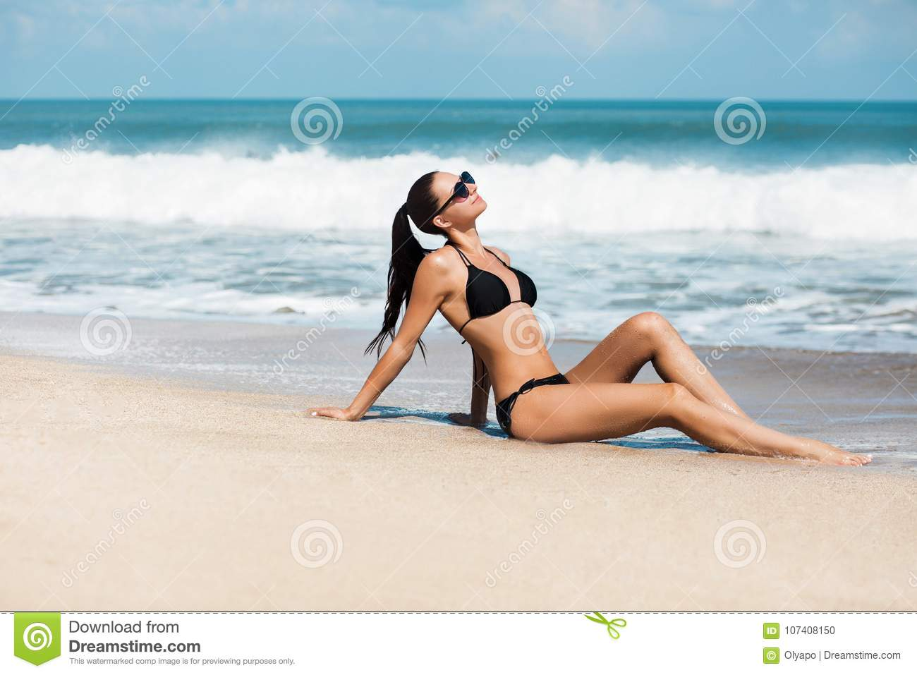 09c24c0f06 Close-up beautiful luxury slim girl in a black bikini on the beach the  ocean. Outdoor summer lifestyle image of young pretty woman outfit and  sunglasses, ...