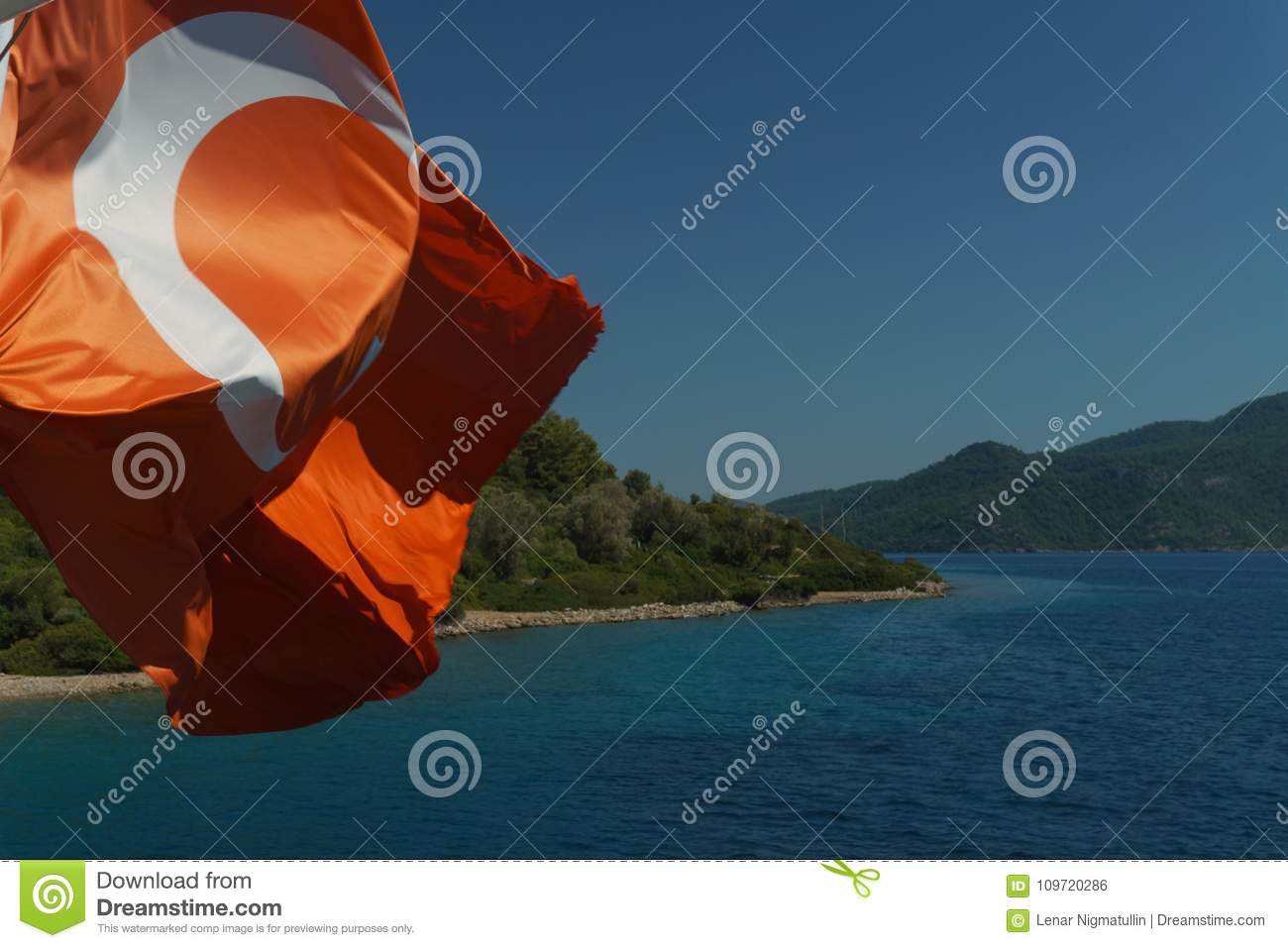 Waving flag of Turkey against the sea on a clear day
