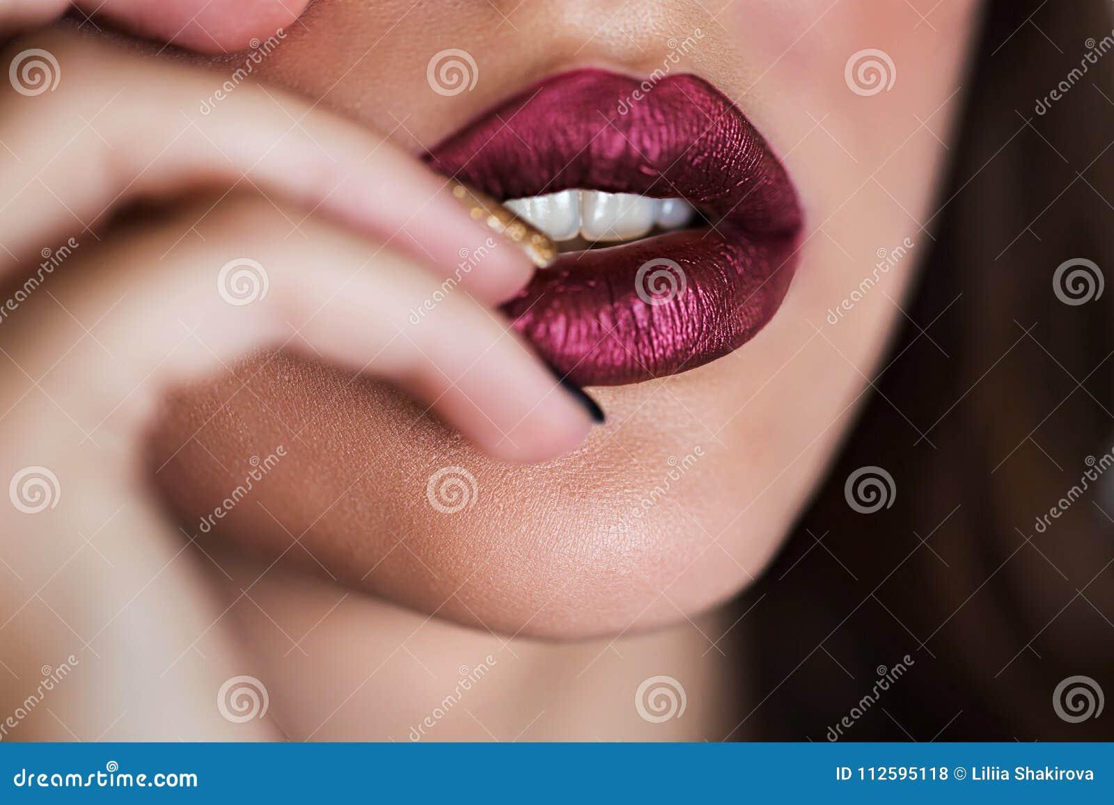 Close up of beautiful woman lips with lipstick. Open mouth. Cosmetology, fashion makeup concept. Beauty studio shot.