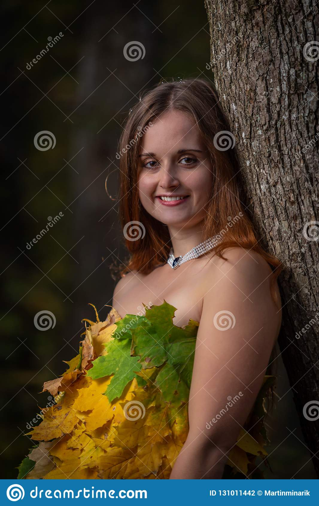 Close up on beautiful young girl with long hair leaning on tree, wearing dress made from colorful leaves in the autumn forest
