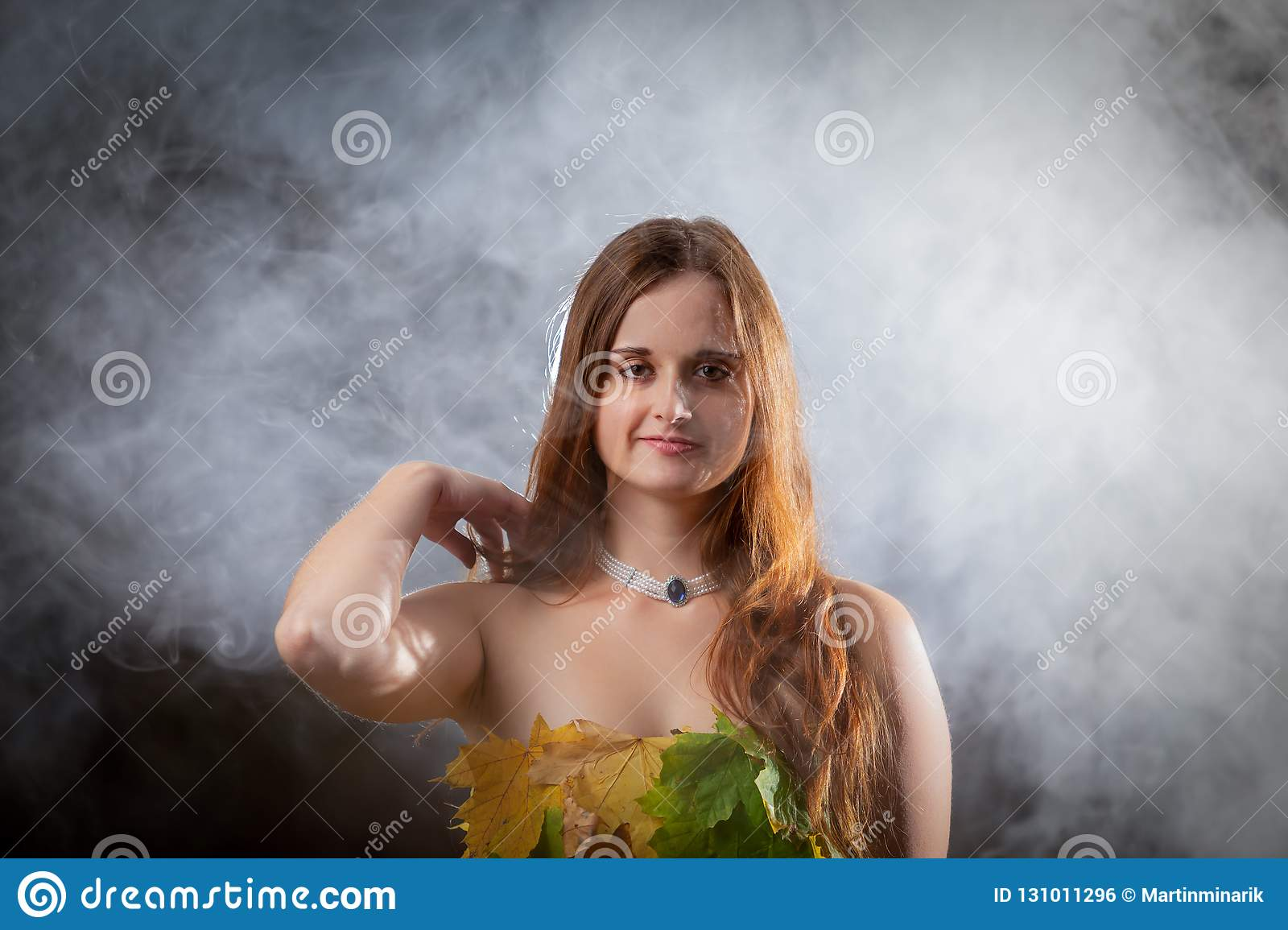 Close up on beautiful young girl with long hair wearing dress made from colorful leaves in the autumn misty forest