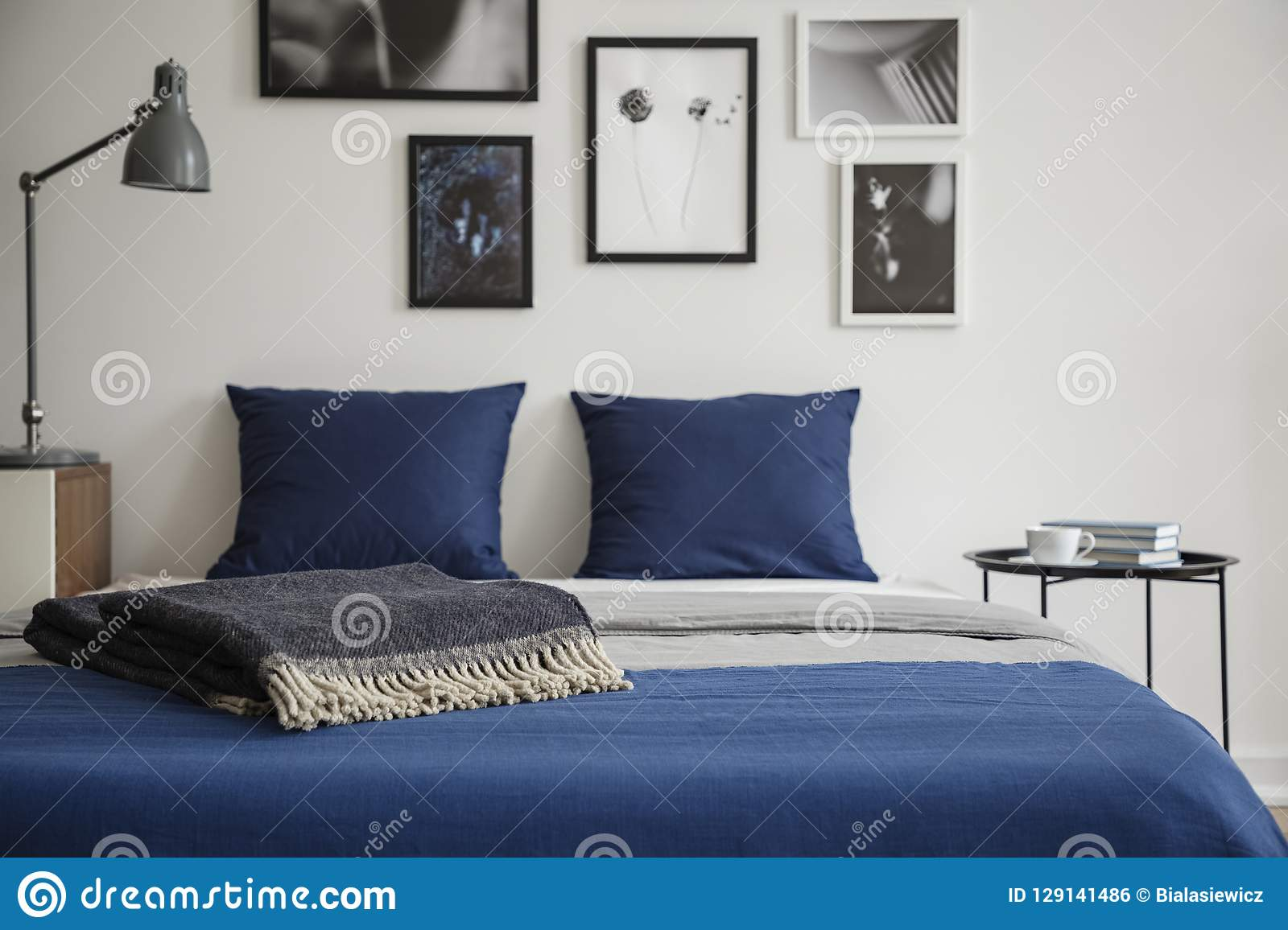 Close-up of bed with blue bedding and dark colored blanket. Bedside table with books and coffee next to it.